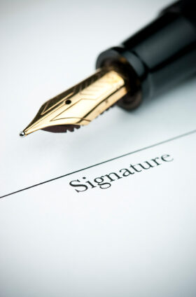 Pen resting above signature line of document. Focus on tip of pen nib.
